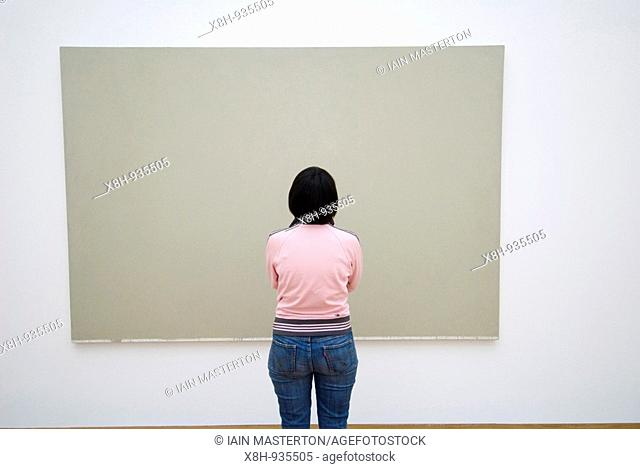 Visitor looking at modern art paintings at Hamburger Bahnhof modern art gallery in Berlin