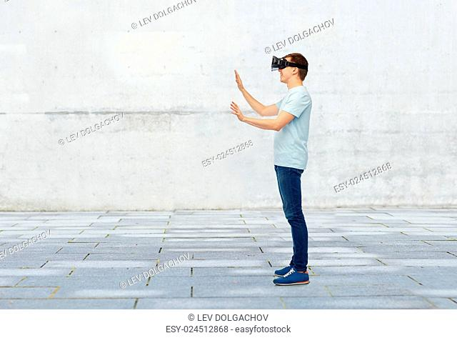 3d technology, virtual reality, entertainment, cyberspace and people concept - happy young man with virtual reality headset or 3d glasses playing game and...