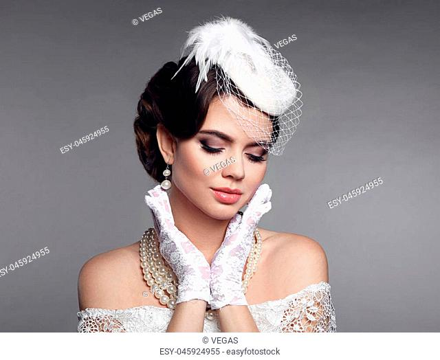 Elegant style. Brunette woman with beauty makeup and hairstyle, pearls jewelry set wears in hat and lace gloves posing isolated on studio gray background