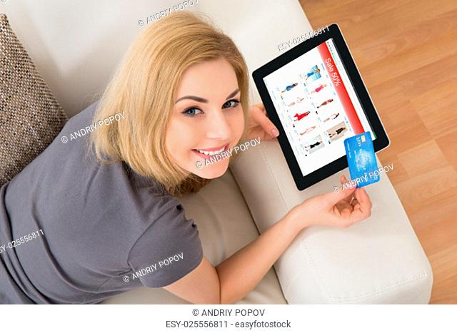 Young Beautiful Woman On Sofa Buying Online With Credit Card
