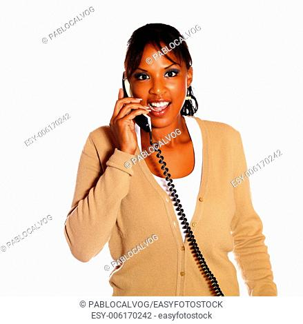 Charming female talking on phone looking at you against white background