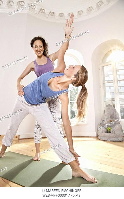 Yoga instructor helping woman with Urdhva Virabhadrasana pose