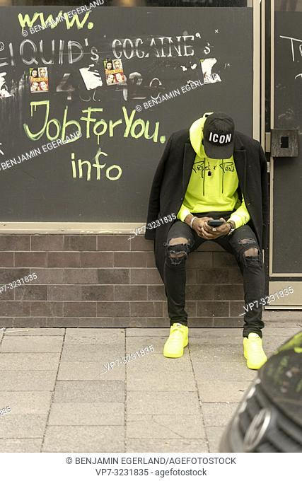 young stylish man looking for job, using smartphone, leaning on wall at street, in city Munich, Germany