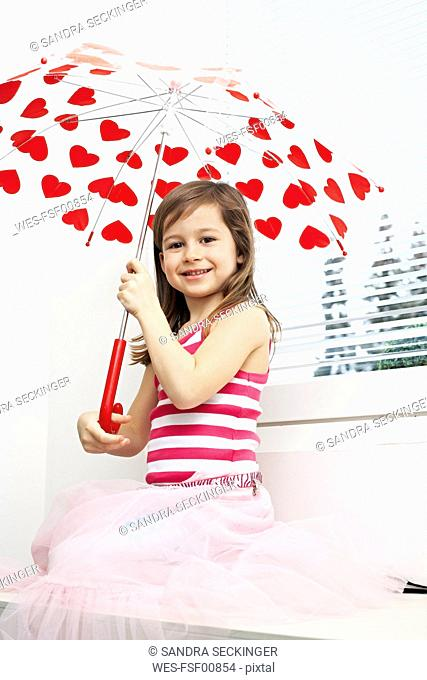 Portrait of smiling little girl with umbrella