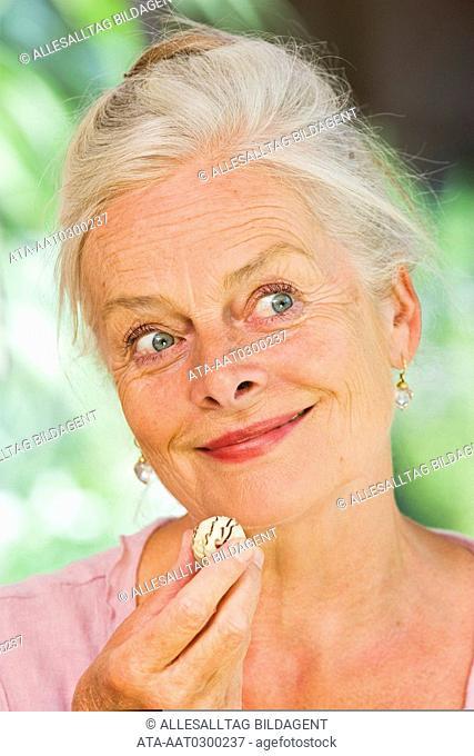 Elderly lady eating choc