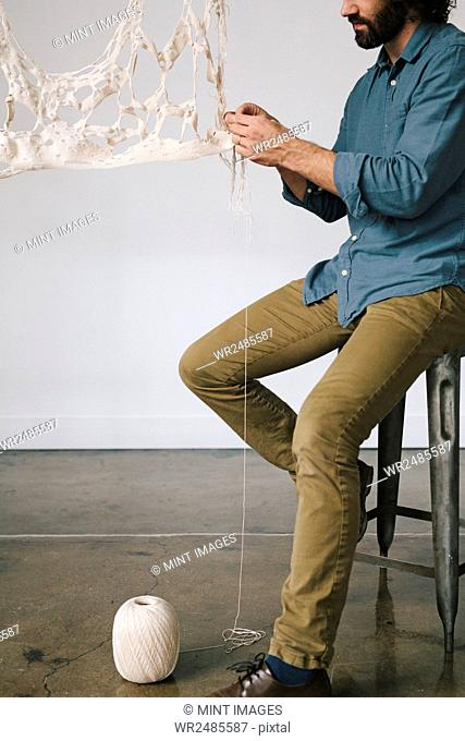 An artist seated working on an art piece, woven fabric and thread