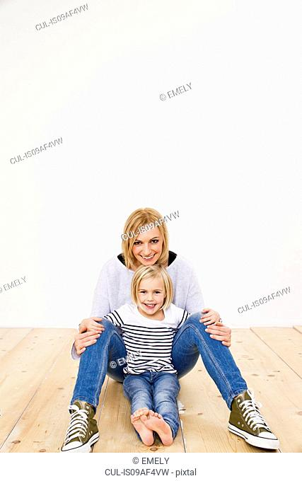 Studio portrait of mother and daughter sitting on floor