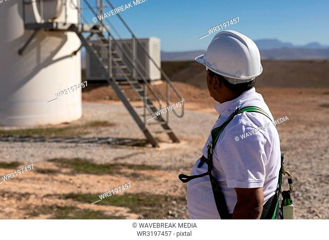 Engineer standing near a wind mill
