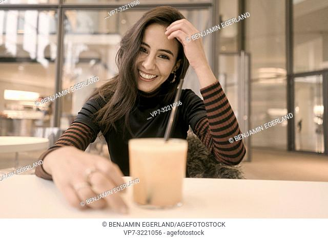 portrait of happy woman with healthy juice glass enjoying break at table in café, candid emotional, unposed, in Munich, Germany