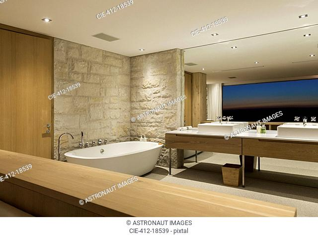 Modern bathroom with soaking tub at night