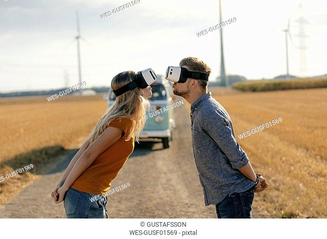 Young couple wearing VR glasses kissing at camper van in rural landscape