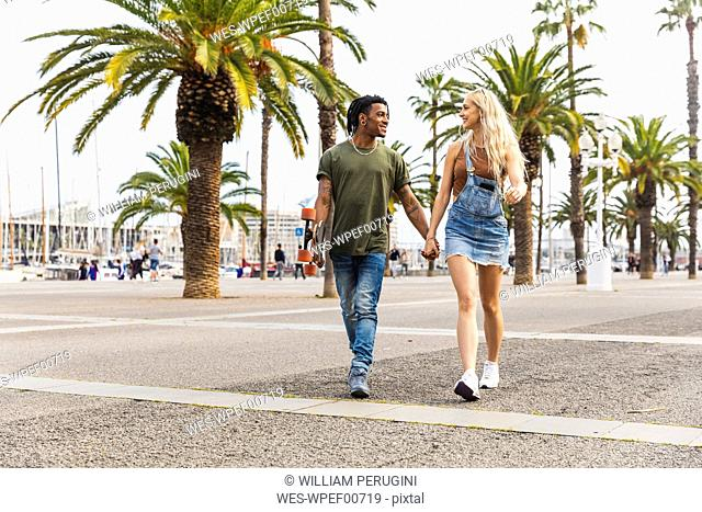 Spain, Barcelona, multicultural young couple walking hand in hand on promenade