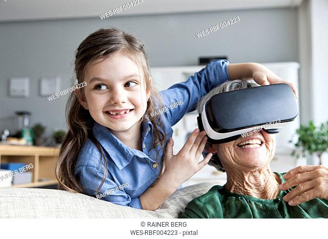 Senior woman and her granddaughter having fun with Virtual Reality Glasses at home