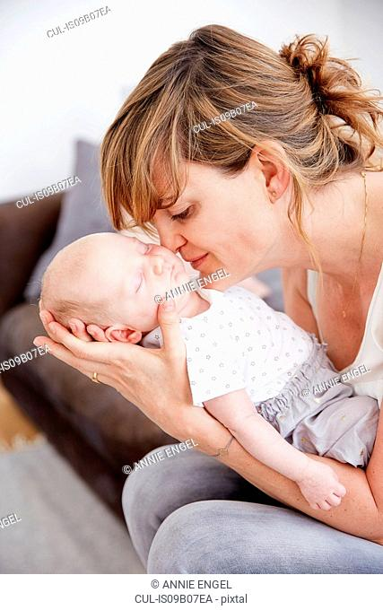 Mother kissing sleeping baby daughter