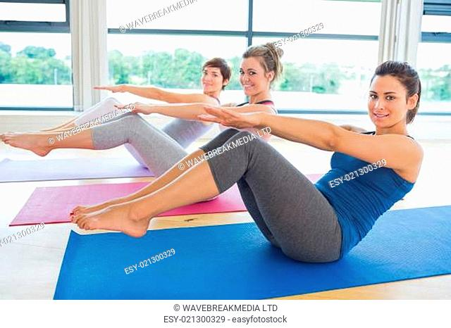 Happy women in yoga class doing boat pose in fitness studio