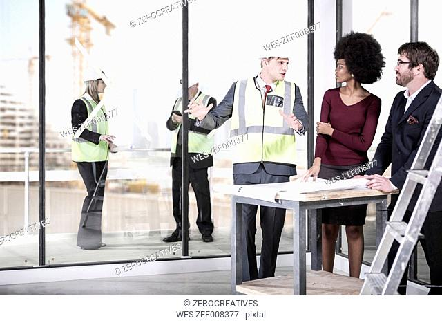 Architect wearing safety vest talking to man and woman
