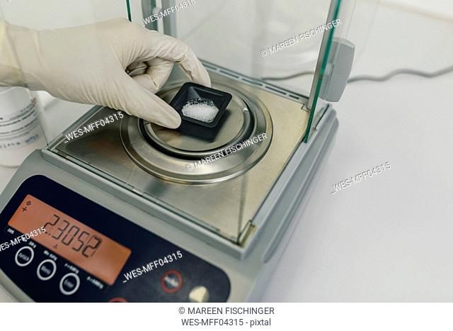 Hand with protective glove using scales in laboratory of a pharmacy