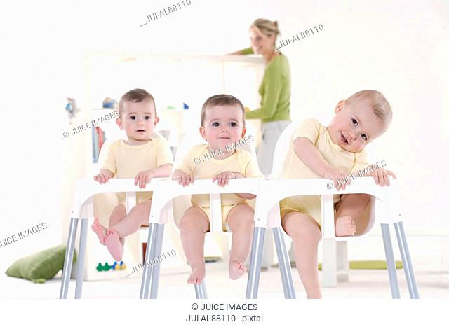 Triplet babies sitting in high chairs