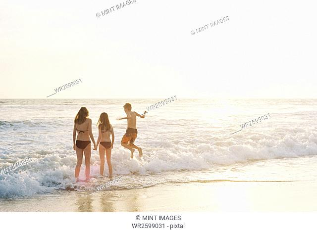 Three children playing on a sandy beach by the ocean