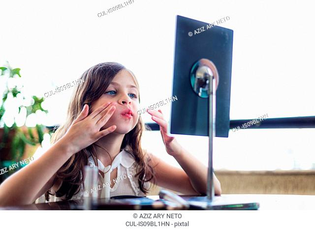 Girl touching cheeks in front of mirror