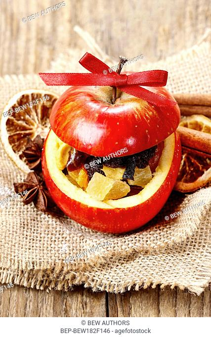 Red christmas apple stuffed with dried fruits in honey