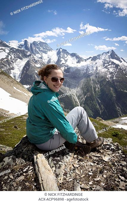 Female hiker smiling in mountainous environment, Glacier National Park, British Columbia, Canada