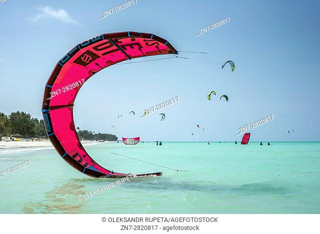 Kitesurfing on a beach of Paje, Zanzibar, Tanzania. Paje is a windy place for good kiting and at the same time it is safe for beginners training