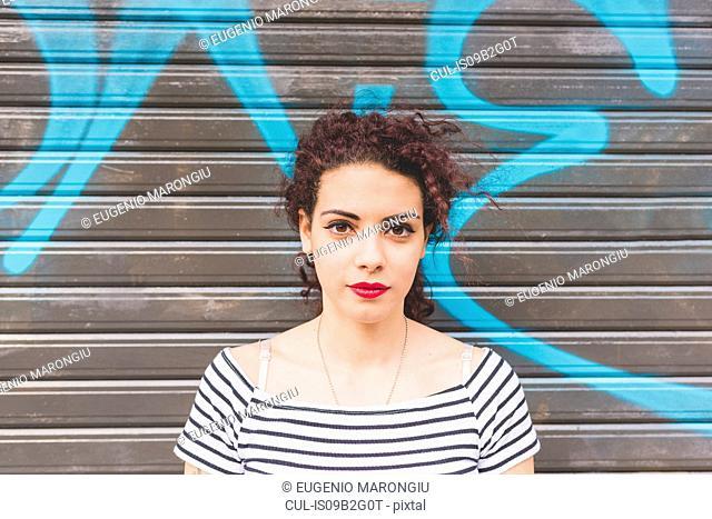 Portrait of woman in front of graffiti shutter