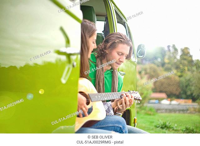 Couple playing guitar in van