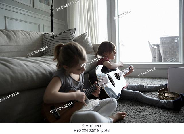 Sisters playing guitar and ukulele in living room