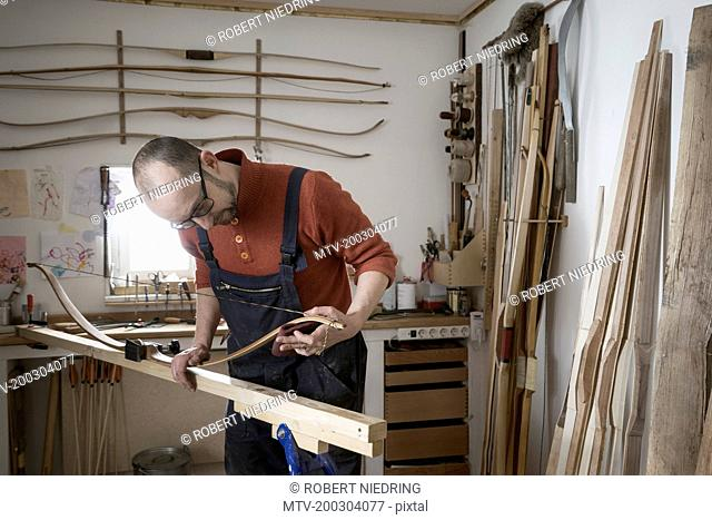 Male bow maker making bow in workshop, Bavaria, Germany
