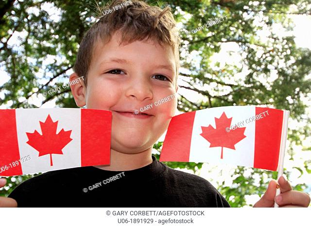 a five year old boy holding up Canadian flags in celebration of Canada Day July 1st in Canada
