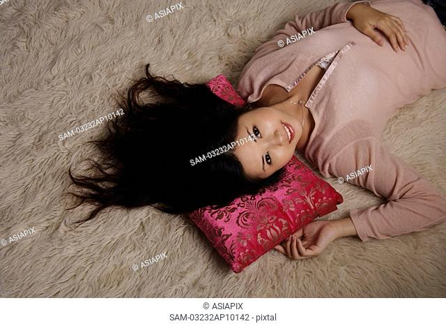 Chinese woman laying on rug