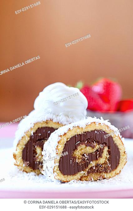 Slices of chocolate coconut cake roll decorated with whipped cream, with strawberries in the background
