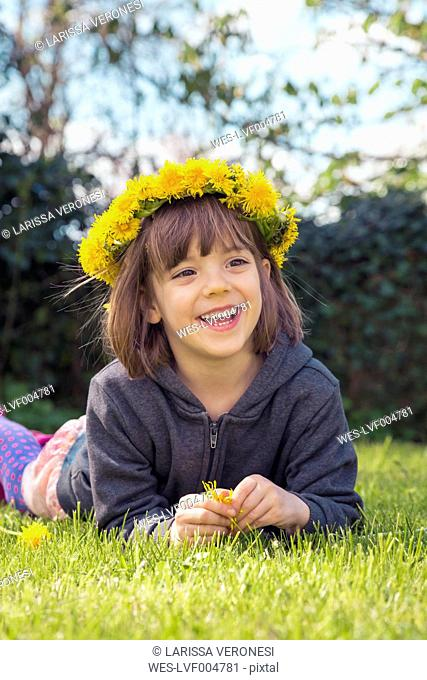 Portrait of smiling little girl lying on meadow wearing floral wreath of dandelions