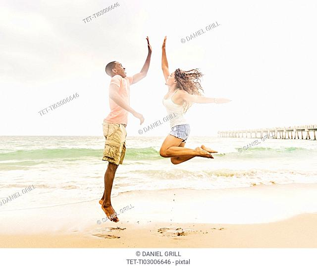 Young couple playing on beach