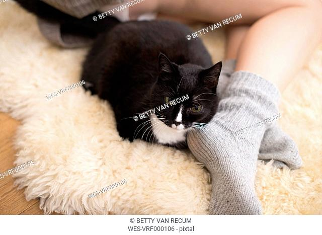 Young woman with cat lying on carpet