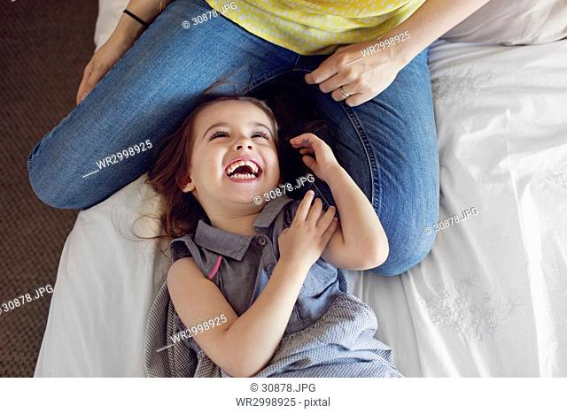 High angle view of woman sitting on a bed, playing with smiling young girl