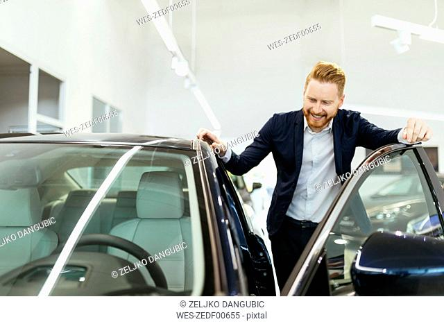 Customer looking at car in car dealership