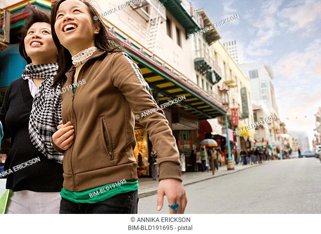 Chinese mother and daughter walking down urban street