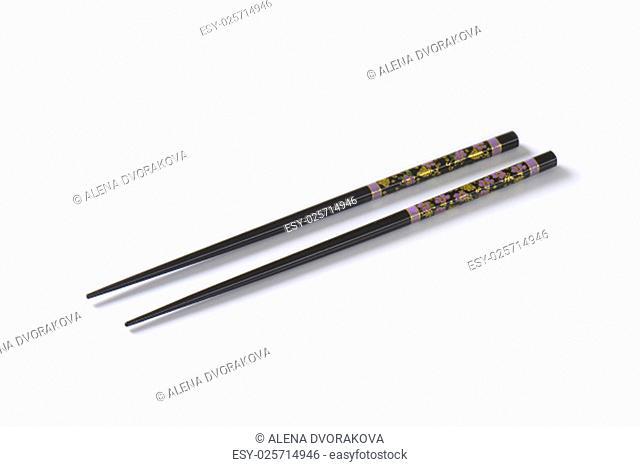 pair of black chopsticks on white background