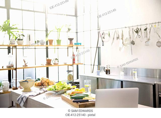 Interior of domestic kitchen with vegetables on kitchen counter