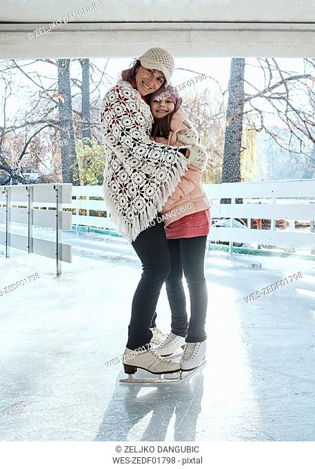 Mother and daughter embracing on the ice rink