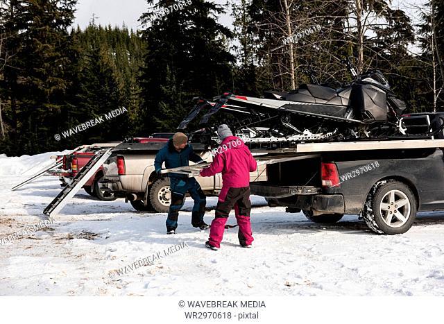 Couple loading snowmobile on van