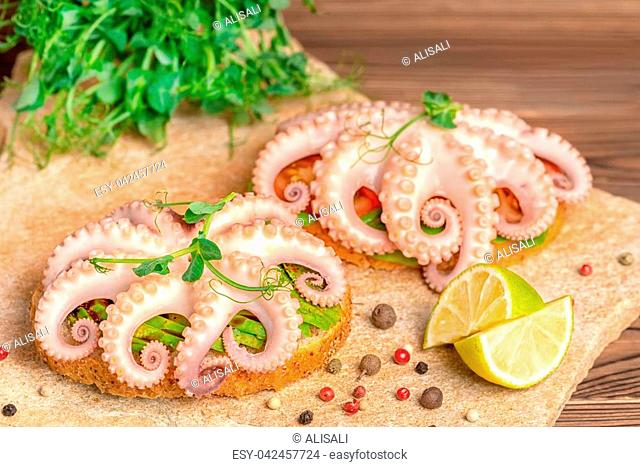 close up of sandwiches with octopus and bread toast decorated lime, sprigs of pea leaves and dry peppers, natural seafood