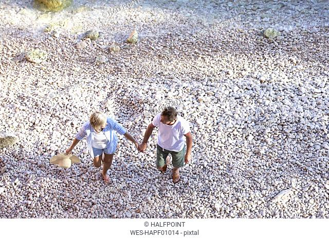 Top view of senior couple walking on the beach