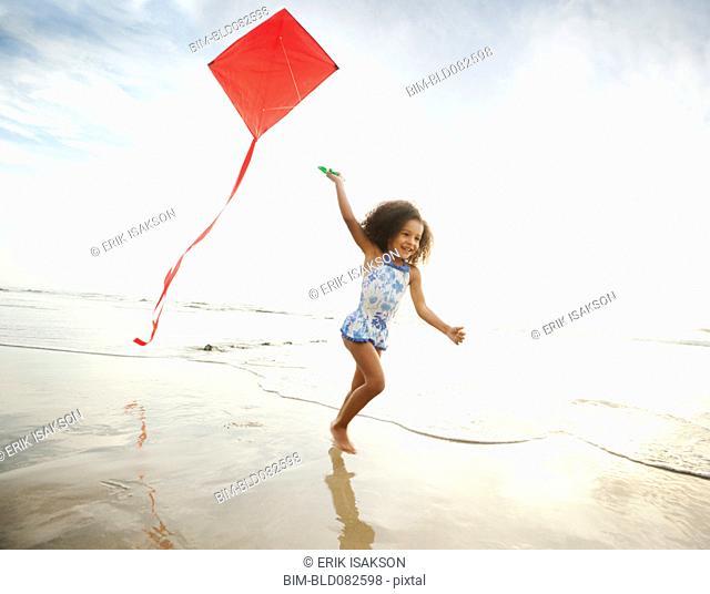 Mixed race girl running with kite on beach