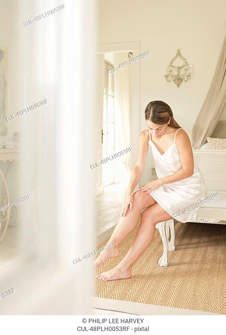 Woman moisturizing her legs
