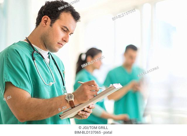Hispanic nurse reading medical chart in hospital