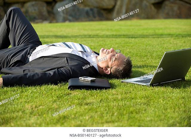 businessman relaxing in meadow